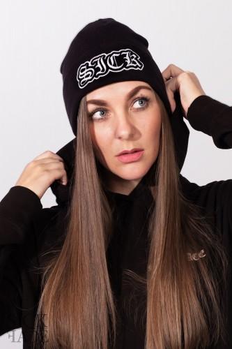 Černá zimní čepice značky SickFace s nápisem SICK vyfocená na modelce.